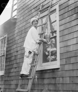 Woman On Ladder Painting House